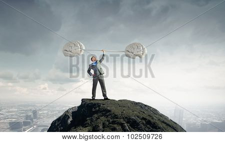 Confident businessman lifting above head barbell as symbol of great mind