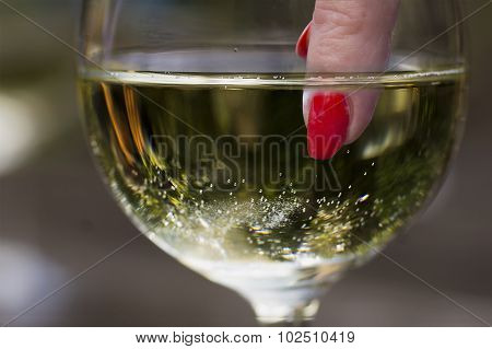 Woman's Finger With Red Nail In Wineglass