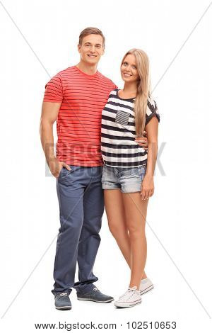 Full length portrait of a casual young couple hugging and posing isolated on white background