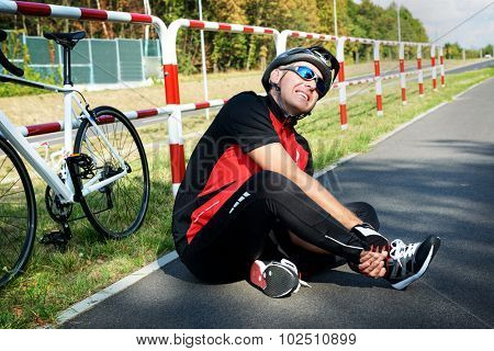 Bicycle accident. Biker holding his ankle.