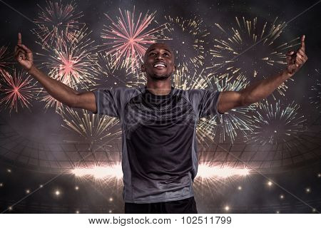 Happy sportsman with arms raised after victory against fireworks exploding over football stadium