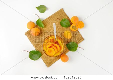 overhead view of compote apricots in the glass bowl with spoon, standing on the straw linen