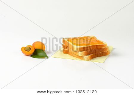 three stacked white toasts with apricot jam