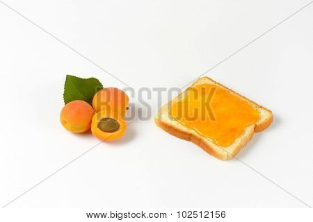 white toast with apricot jam and fresh apricots