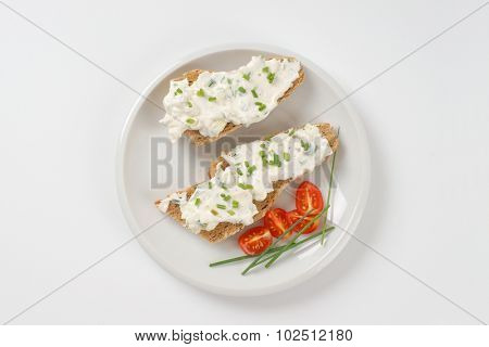 open faced sandwich with chives spread on white plate