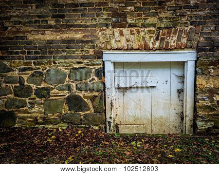 Short, White, Wooden Door in Brick-and-Stone Wall