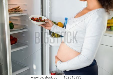Midsection of pregnant woman keeping strawberries in fridge at home in the kitchen