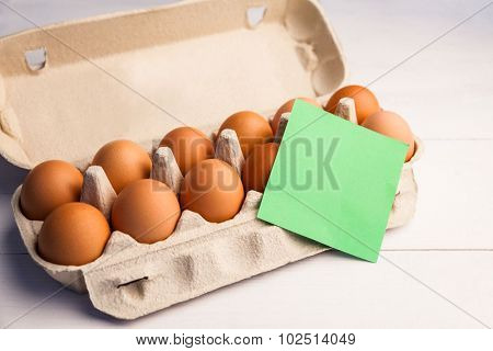Egg carton with a piece of green paper on the table