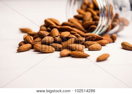 Fresh almonds spilling out of jar on the table