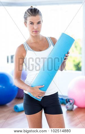 Portrait of beautiful woman holding yoga mat in fitness studio