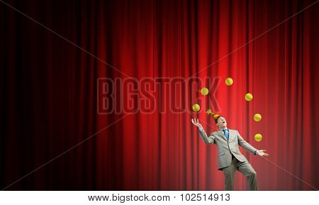 Young businessman in cap on stage juggling with balls