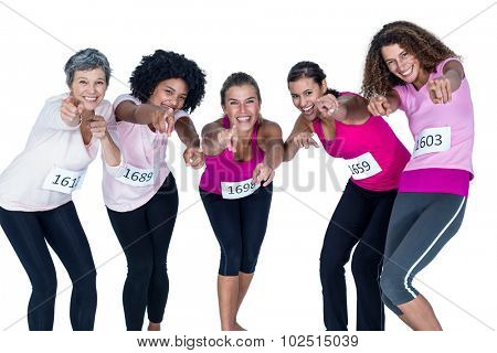 Portrait of smiling athletes pointing while bending against white background