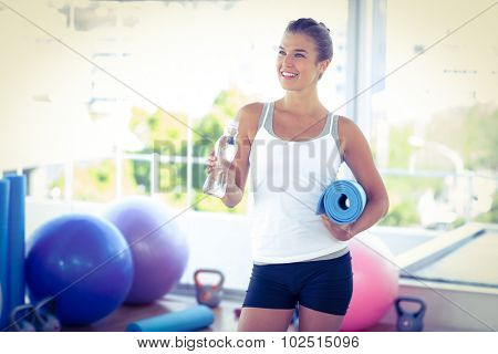 Beautiful woman holding water bottle and yoga mat in fitness studio