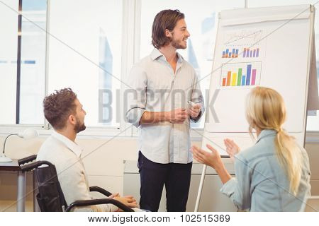 Business people with male colleague looking at multi colored graph during meeting in creative office