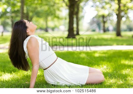 Side view of young woman relaxing on grassland in park