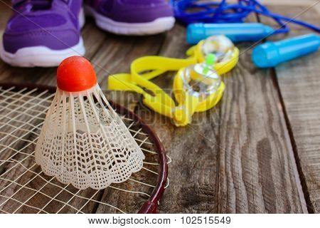 Sports equipment: the birdie is on the racket, skipping rope, swimming goggles and sneakers