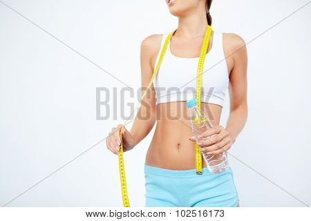 Slender girl with bottle of water and measuring tape