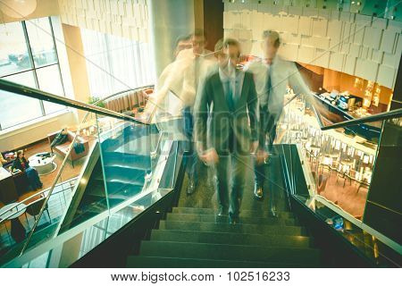 Blurred outlines of businessmen going upstairs