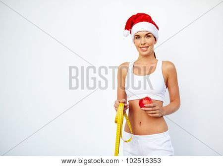 Fit young woman in Santa cap and activewear holding red apple and measuring tape