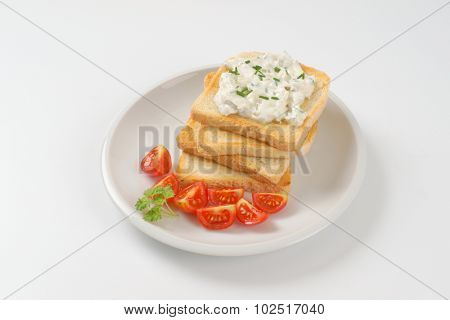 stack of fresh toasts with chives spread on white plate