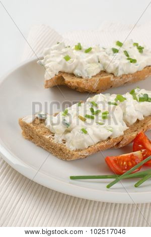 open faced sandwich with chives spread on white plate and place mat