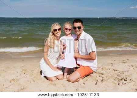 travel, vacation, adoption and people concept - happy family with little girl in sunglasses on summer beach