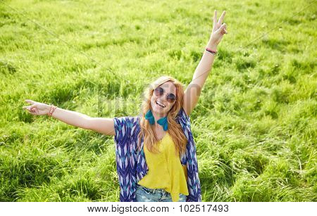 nature, summer, youth culture and people concept - smiling young hippie woman in sunglasses dancing on green field