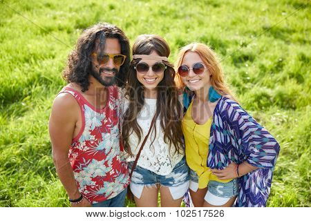 nature, summer, youth culture and people concept - smiling young hippie friends in sunglasses on green field