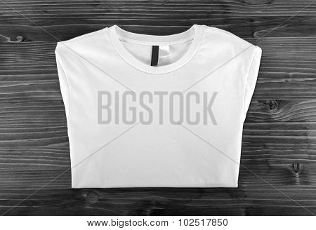White Folded T-shirt Template On A Wooden Background.