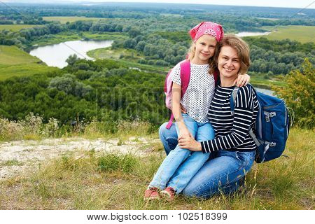 Adult And Child Standing On A Mountaintop Near  River.  Mother With Little Daughter Hiking In Mounta