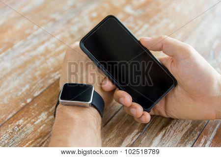 business, technology and people concept - close up of male hand holding smart phone and wearing watch at home