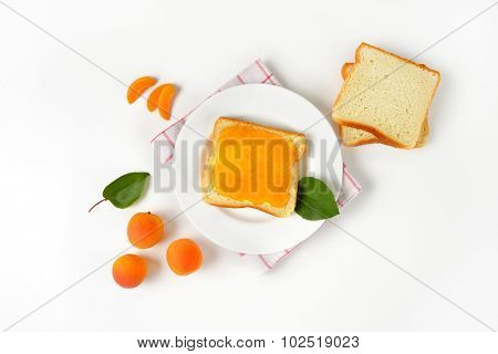 overhead view of plain toasts and toast with apricot jam, accompanied by fresh apricots