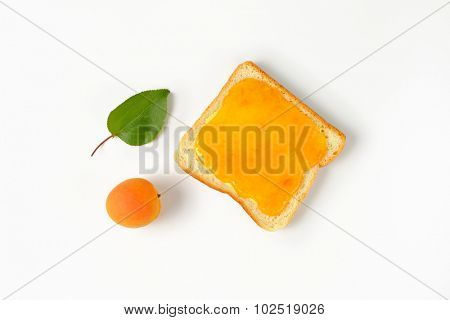 overhead view of one white toast with apricot jam and fresh apricot