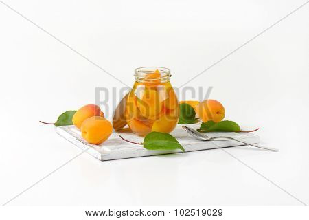 side view of opened glass jar with apricot compote standing on the wooden cutting board and surrounded by fresh apricots and leaves