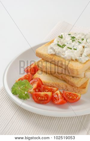 stack of fresh toasts with chives spread on white plate and place mat