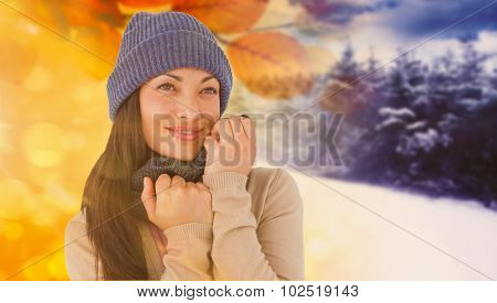 Attractive brunette looking up wearing warm clothes against autumn changing to winter