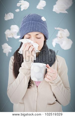 Sick brunette blowing her nose while holding a mug against blue background