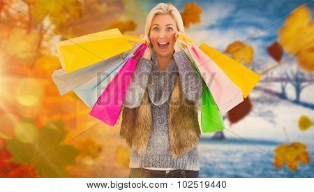 Blonde in winter clothes holding shopping bags against autumn turning to winter
