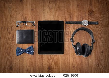 personal stuff and technology and concept - tablet pc computer with blank screen, earphones, wallet, eyeglasses and wristwatch over wooden background