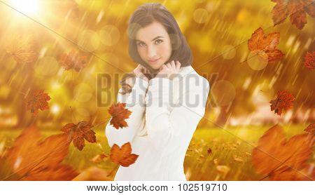 Brunette in white jumper smiling at camera against park