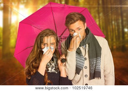 Couple blowing nose while holding umbrella against autumn scene