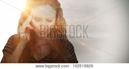 Blonde woman having headache against trees and mountain range against cloudy sky