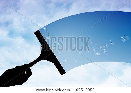 Hand using wiper against digitally generated dandelion seeds against blue sky