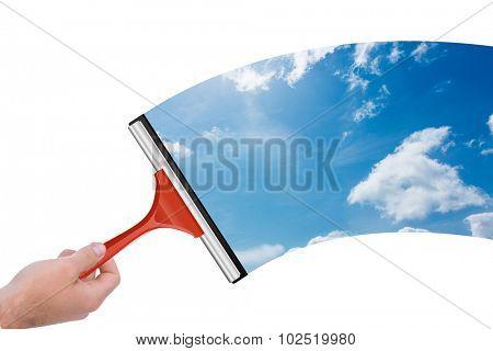 Hand using wiper against blue sky
