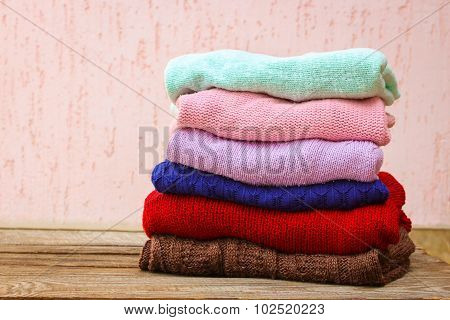 Pile of colorful warm clothes on wooden background.