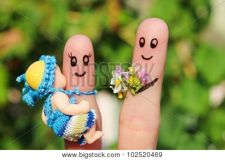 Finger art of a Happy family holding a small child. Concept of husband giving flowers to his wife