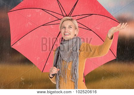 Woman checking to see if its raining against country scene