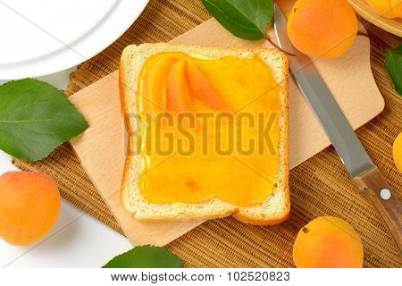 overhead view of white toast greased with apricot marmalade