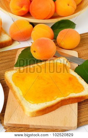 white toast with homemade apricot marmalade accompanied by fresh apricots