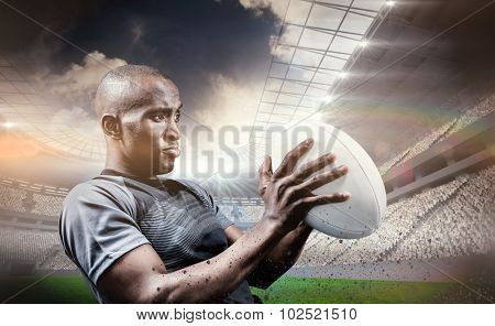 Rugby player looking away while throwing ball against rugby stadium